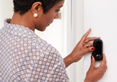 Woman setting a black canary flex home security camera on a white wall