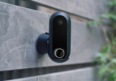 Black Canary Flex security camera mounted on a wooden wall outside